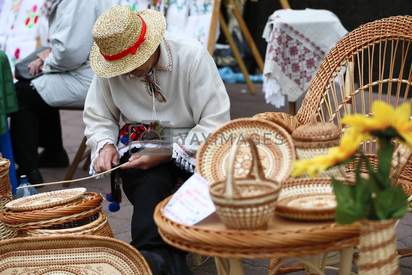 A man in a straw hat braids from a vine.Products from straw. Ethnic handicraft. Man master of straw