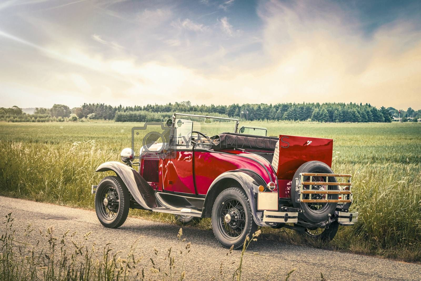 Antique red car on a road in a countryside landscape in the sunset