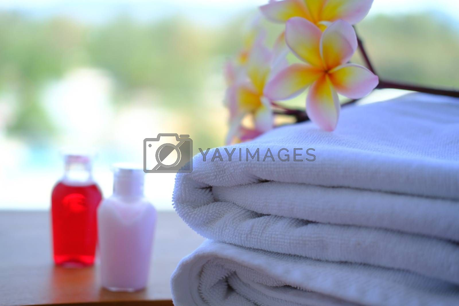 Close up of Stack of towels with fresh Plumeria flowers decor and little bottles of shampoo and hair conditioner. Wellness concept.
