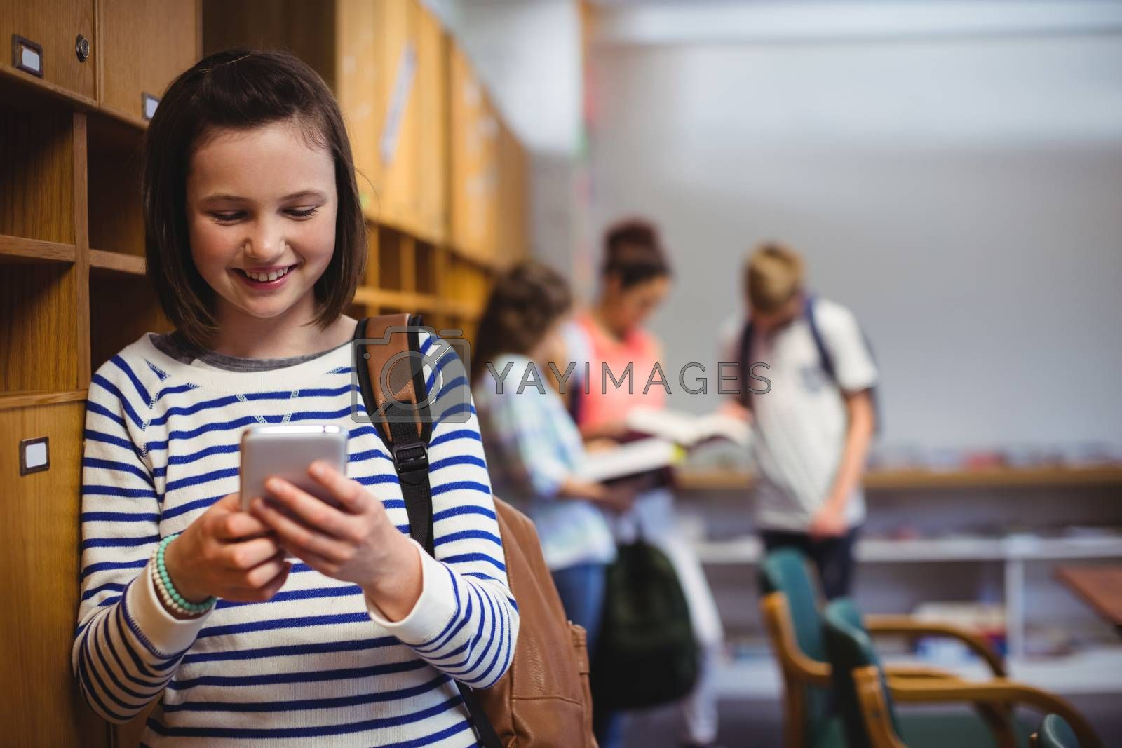 Happy schoolgirl using mobile phone in locker room at school
