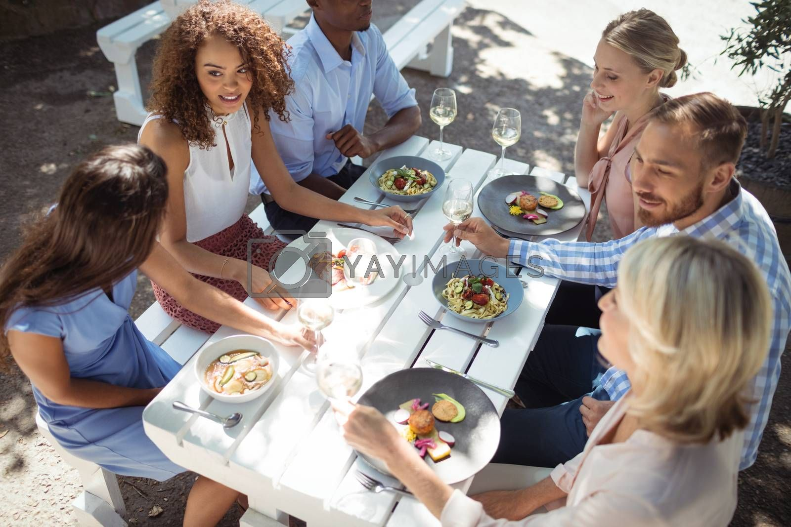 Happy friends interacting with each other while having meal in restaurant