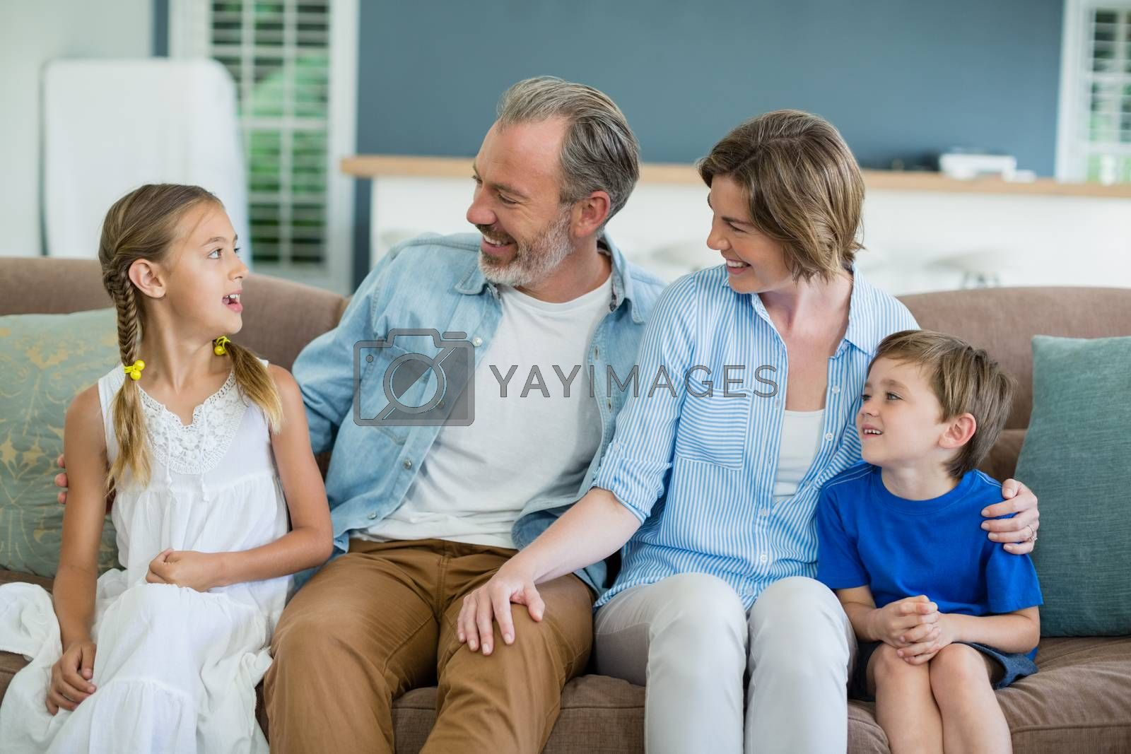 Happy family sitting together on sofa in living room at home