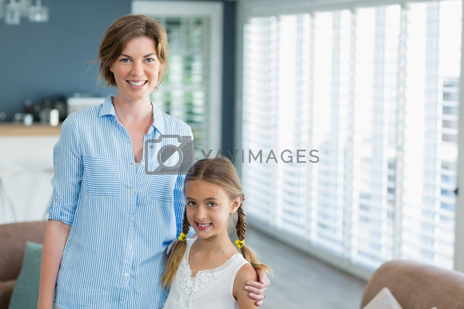 Portrait of smiling mother and daughter standing together in living room at home