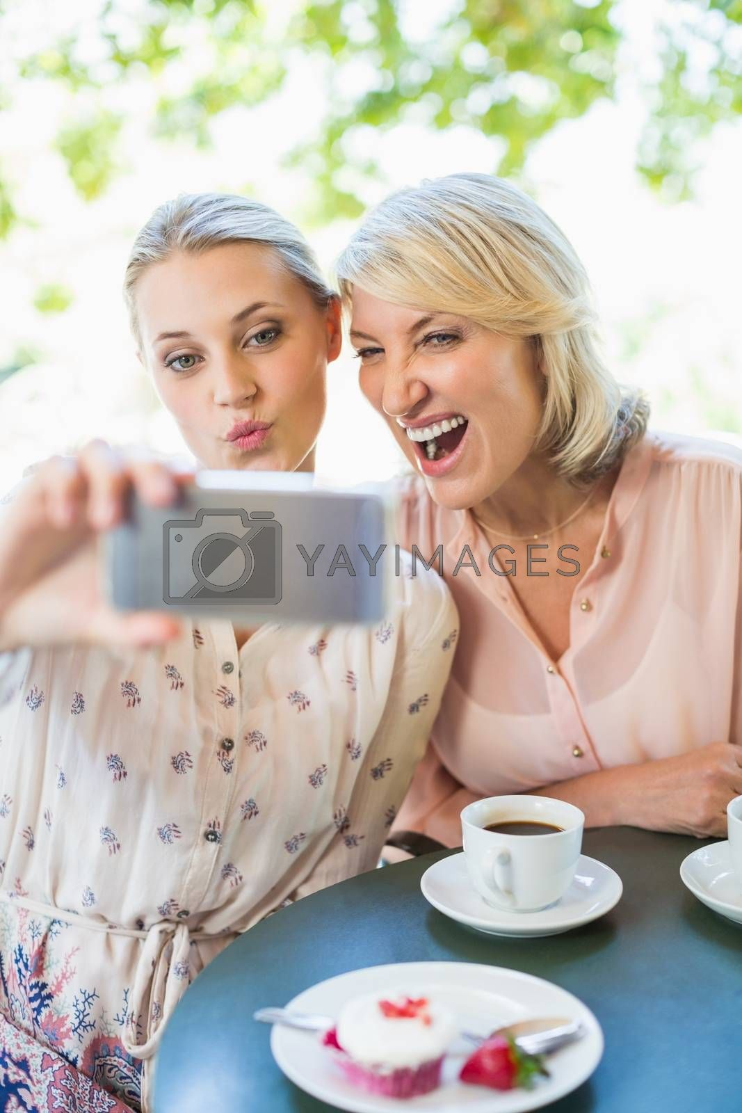 Friends taking a selfie on mobile phone at restaurant