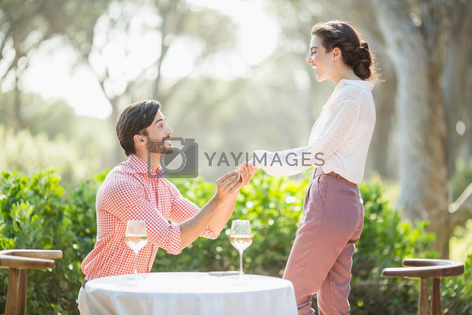 Man proposing a woman with a ring on his knee in the restaurant