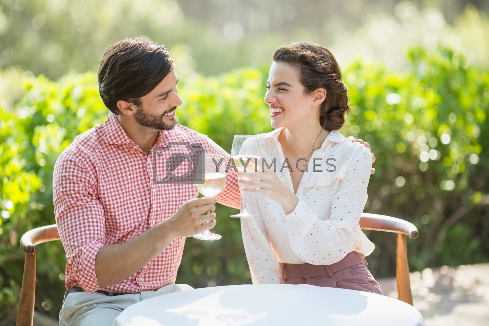 Couple toasting wine glasses while sitting in restaurant