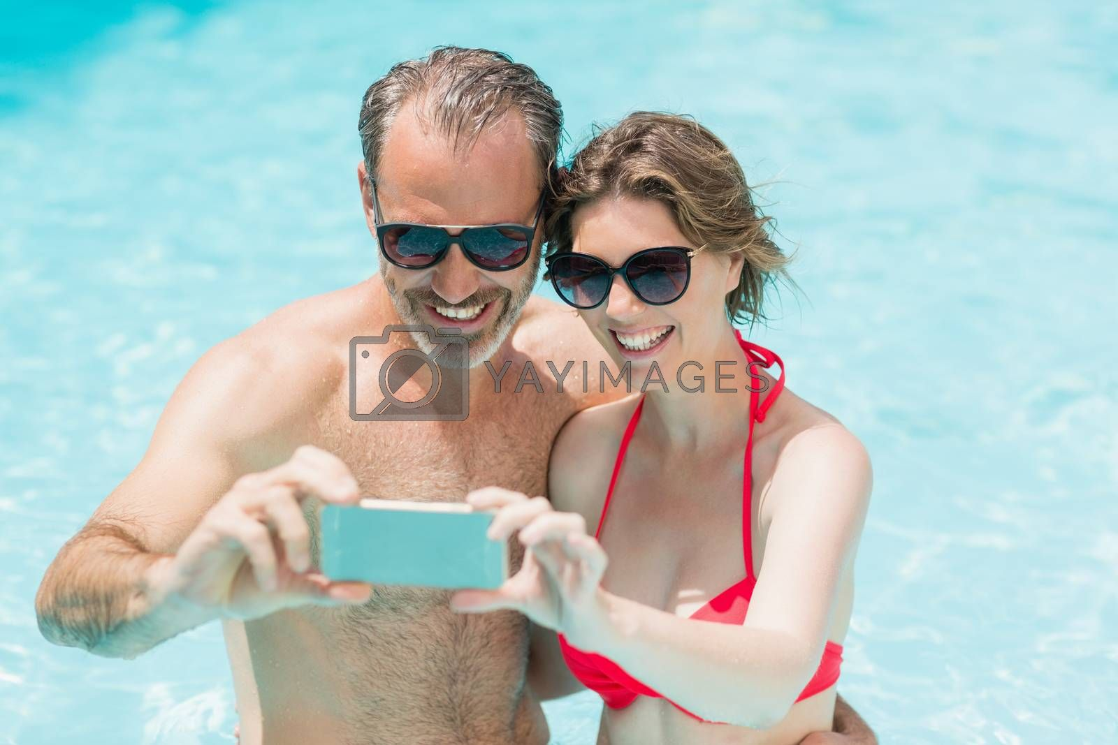 Happy couple taking selfie from mobile phone in pool on a sunny day