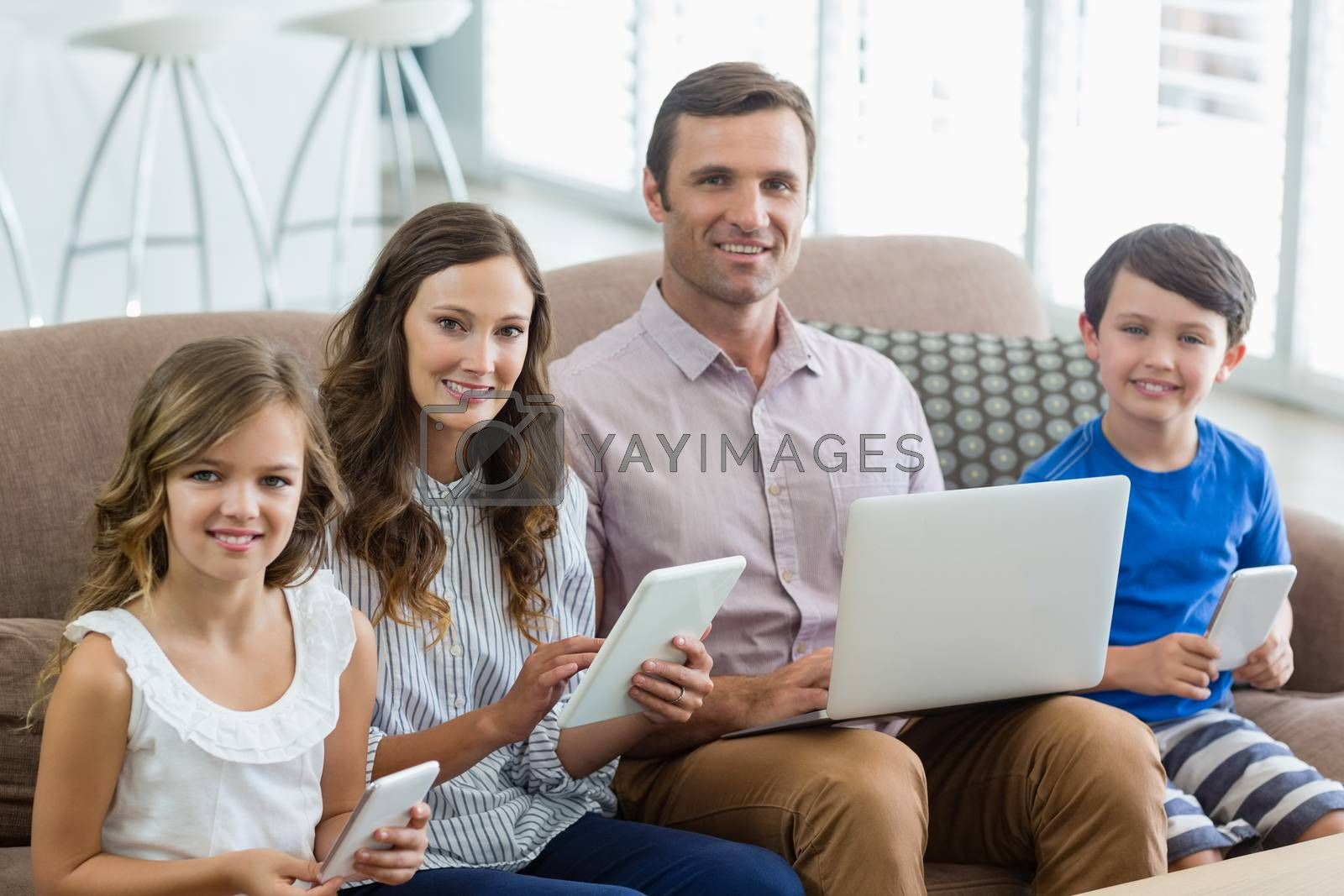Portrait of smiling family using digital tablet, phone and laptop in living room at home