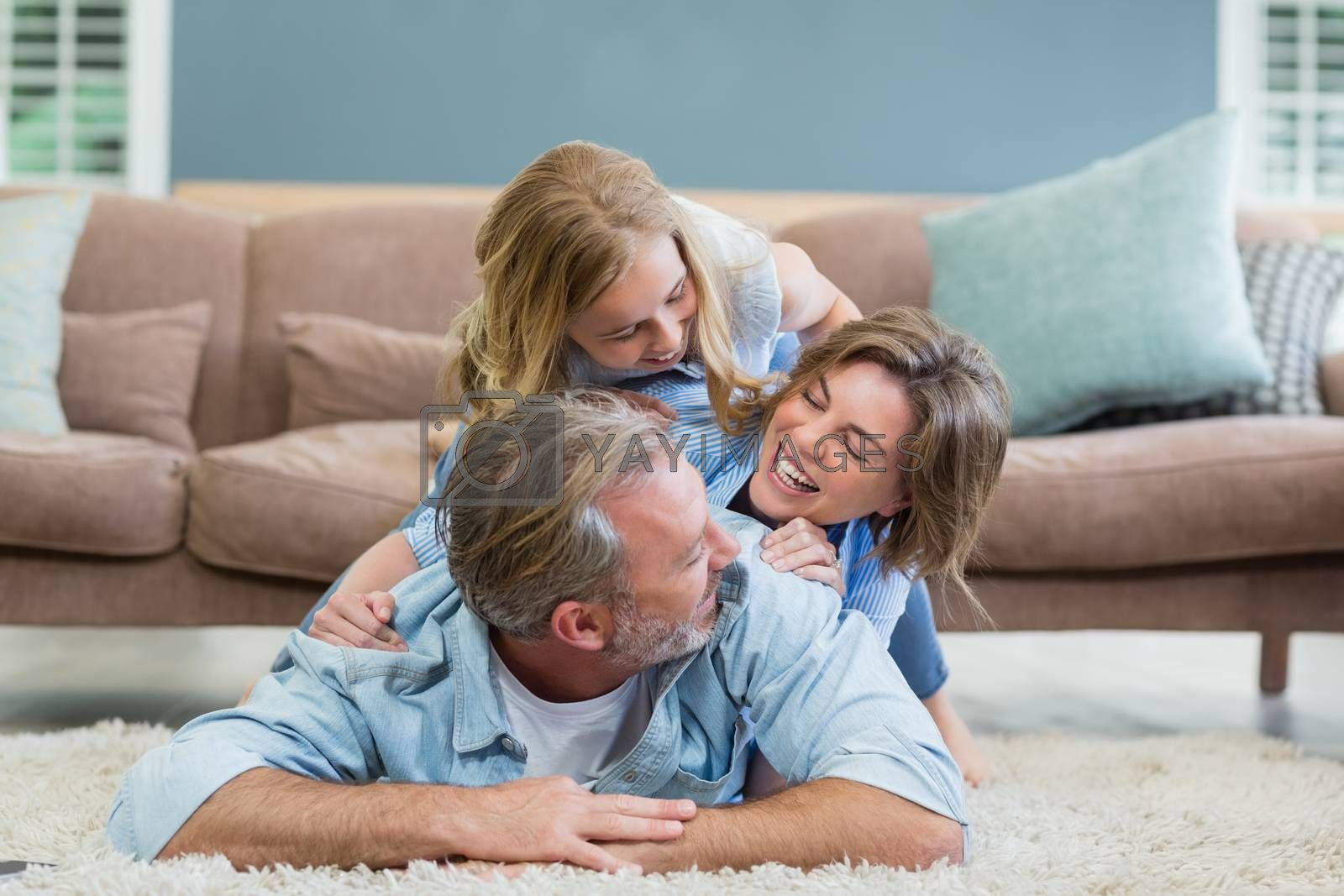 Happy family lying heaped on carpet in living room at home