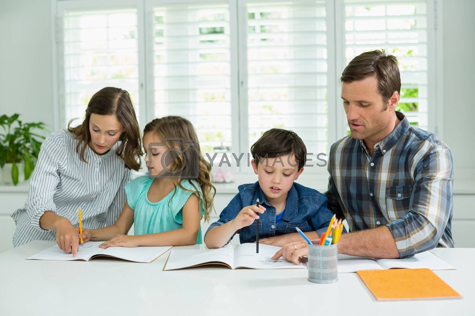 Siblings getting help with homework from parents in living room at home