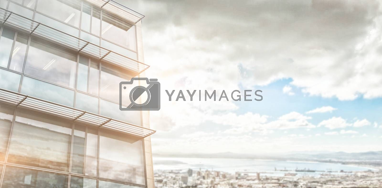 Low angle view of facade of office building against landscape of city and cloudy sky
