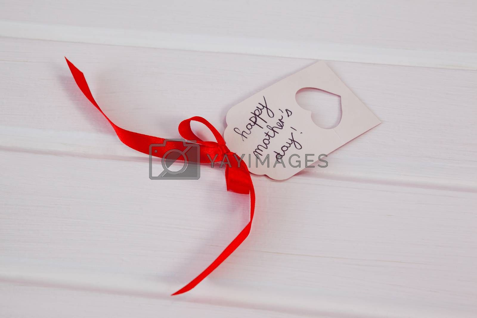 Close-up of happy mothers day card on wooden surface