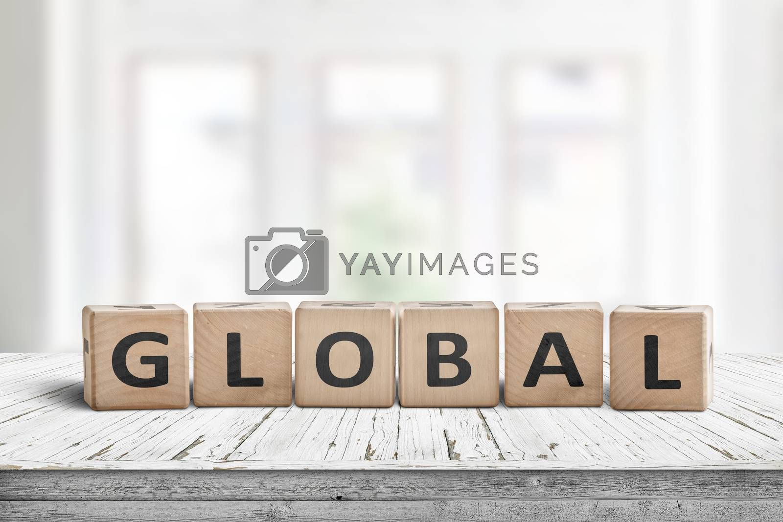 Global sign made of wood in a bright room on a white desk with worn paint