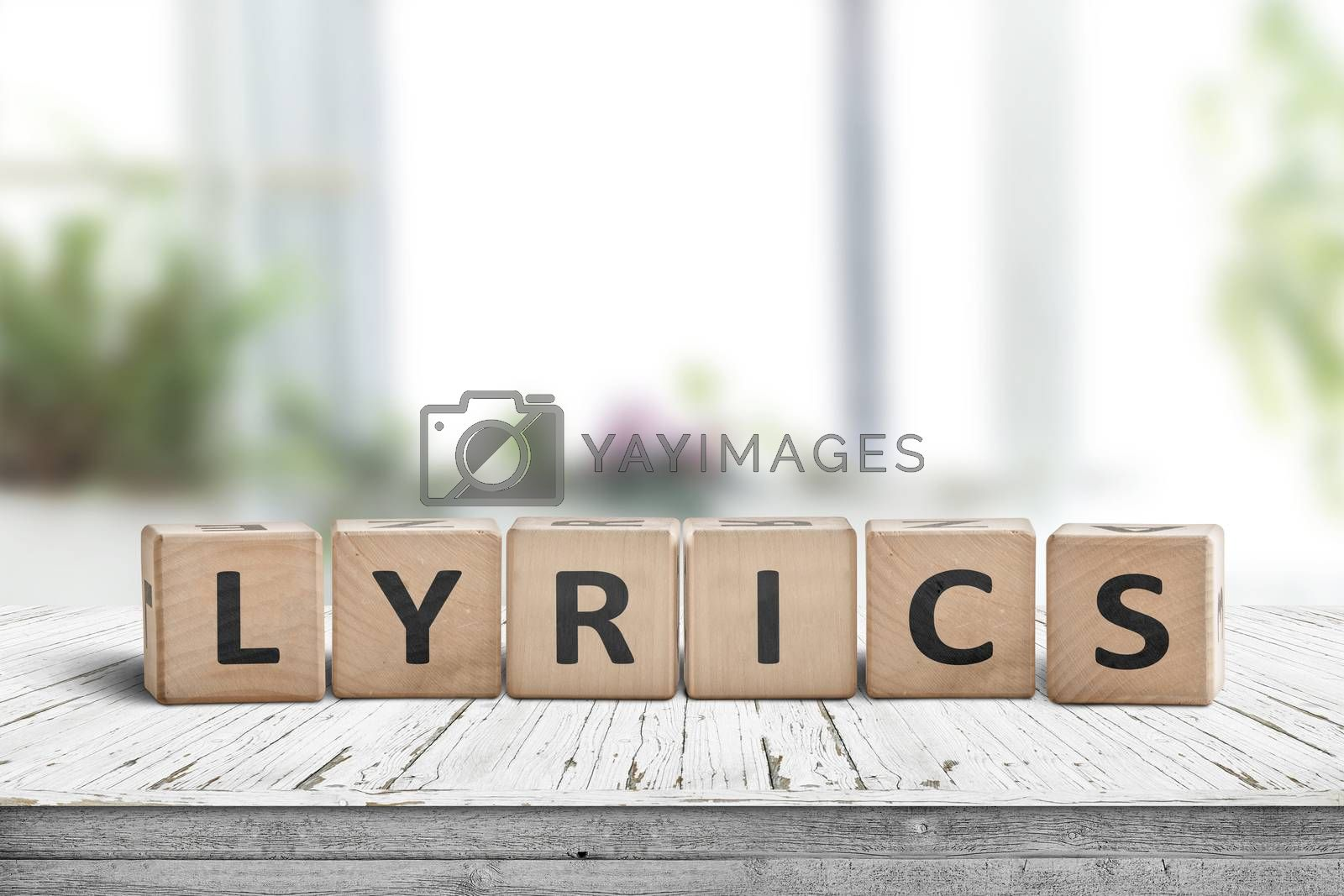 Lyrics sign on a table in a bright room with green plants in the background