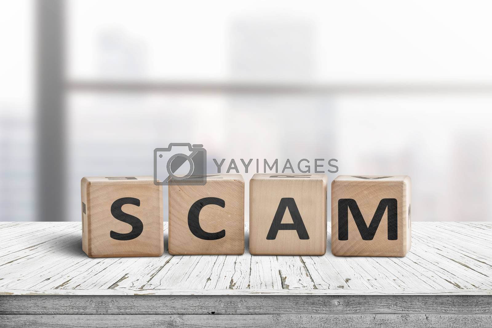 The word scam made of wooden blocks on a table in a bright office room