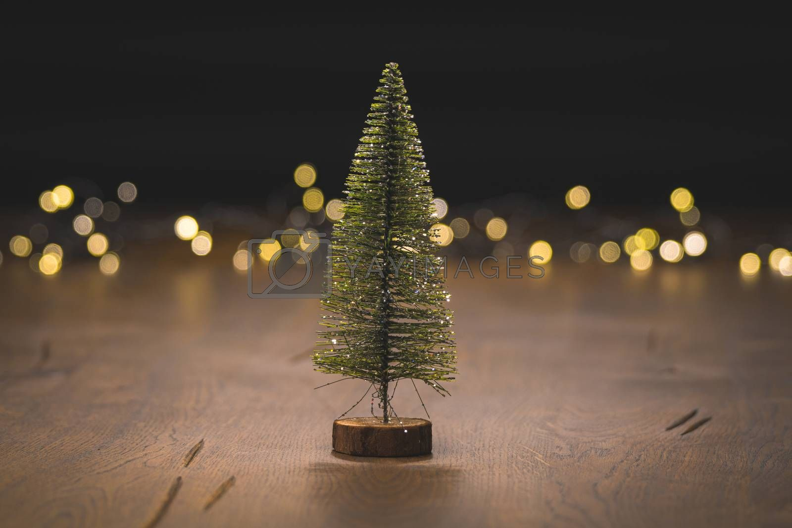 Christmas tree decoration on a wooden surface with golden bokeh lights in the background