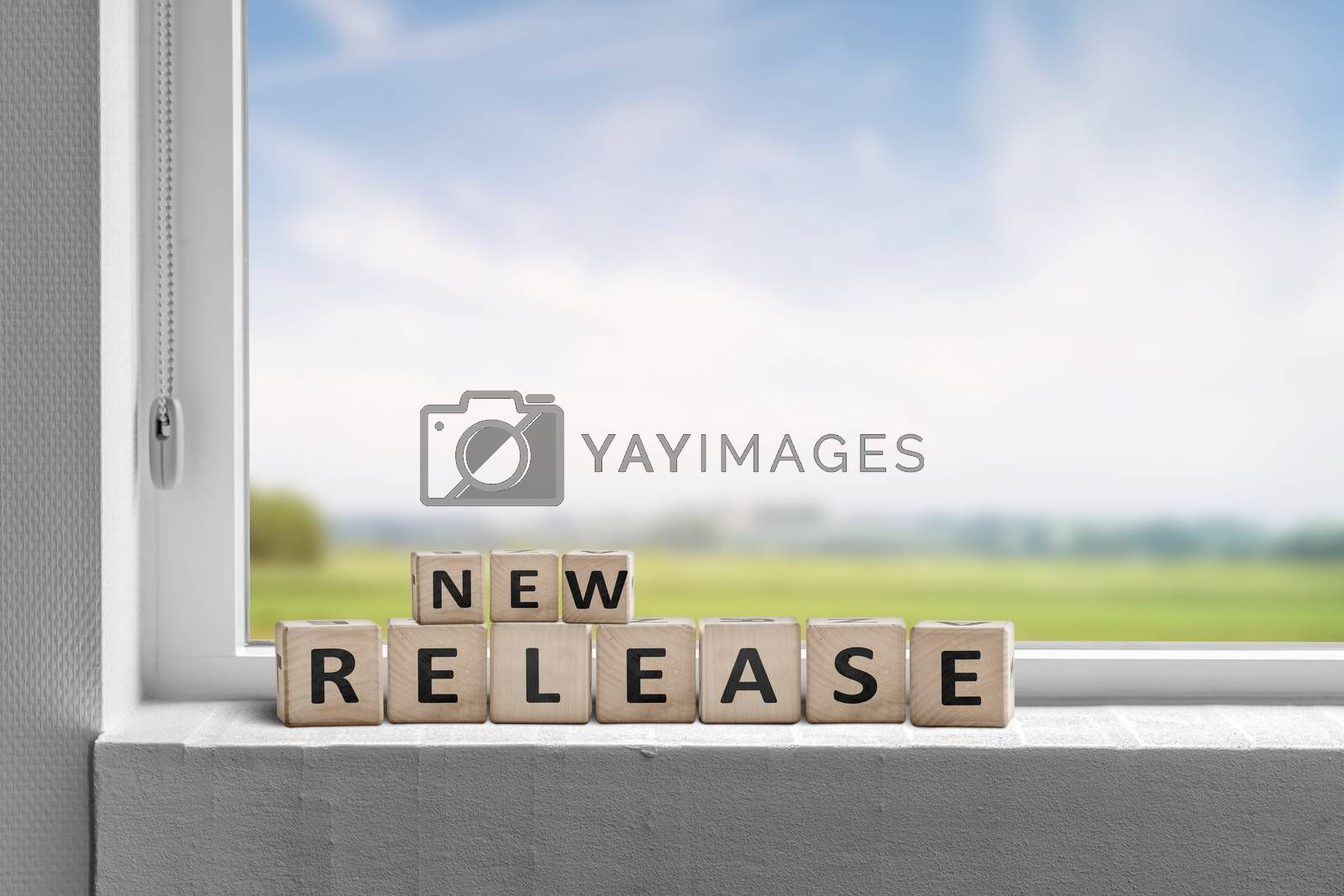 New release sign in a window on a sill with a view to green fields and blue sky
