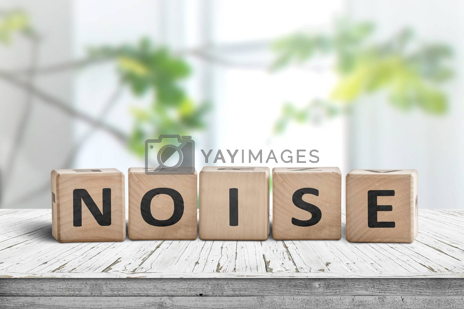 Noise sign made of wood in a bright room with green plants in daylight