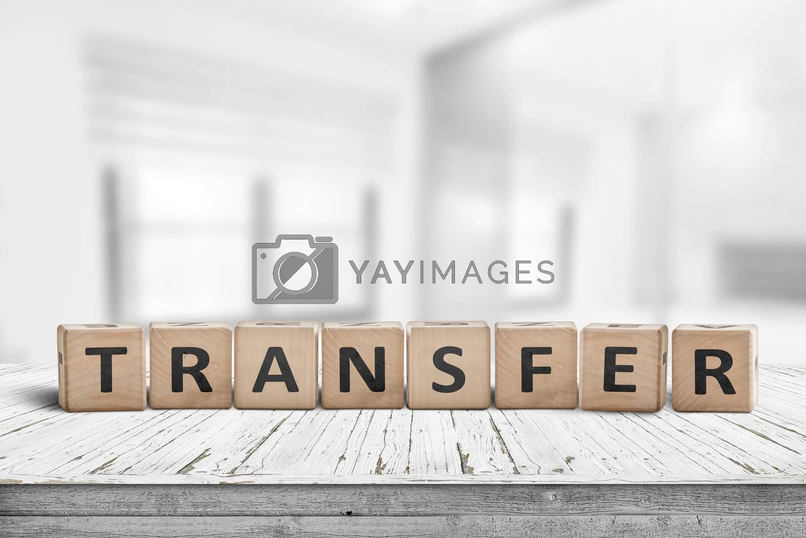 Transfer sign on a wooden table in a bright offce with windows in the background