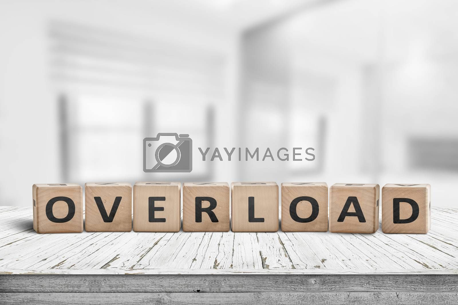 Sign with the word overload in a bright office environment on a wooden table