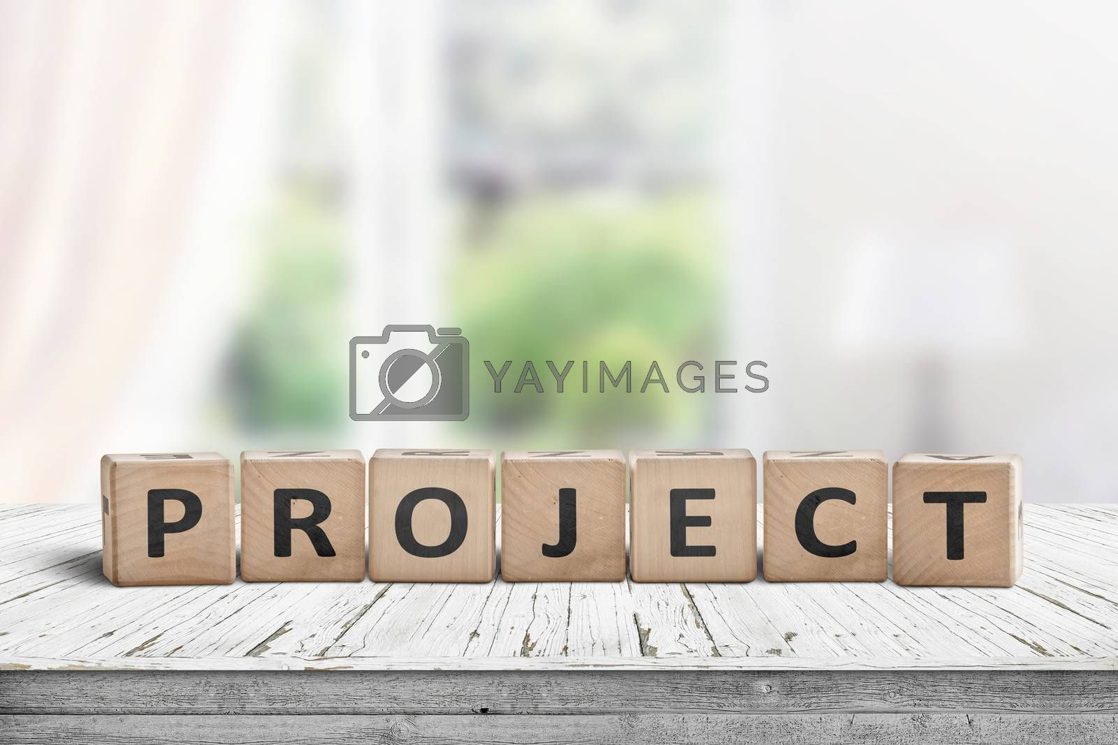 Wooden project sign in a bright room on a table with blocks