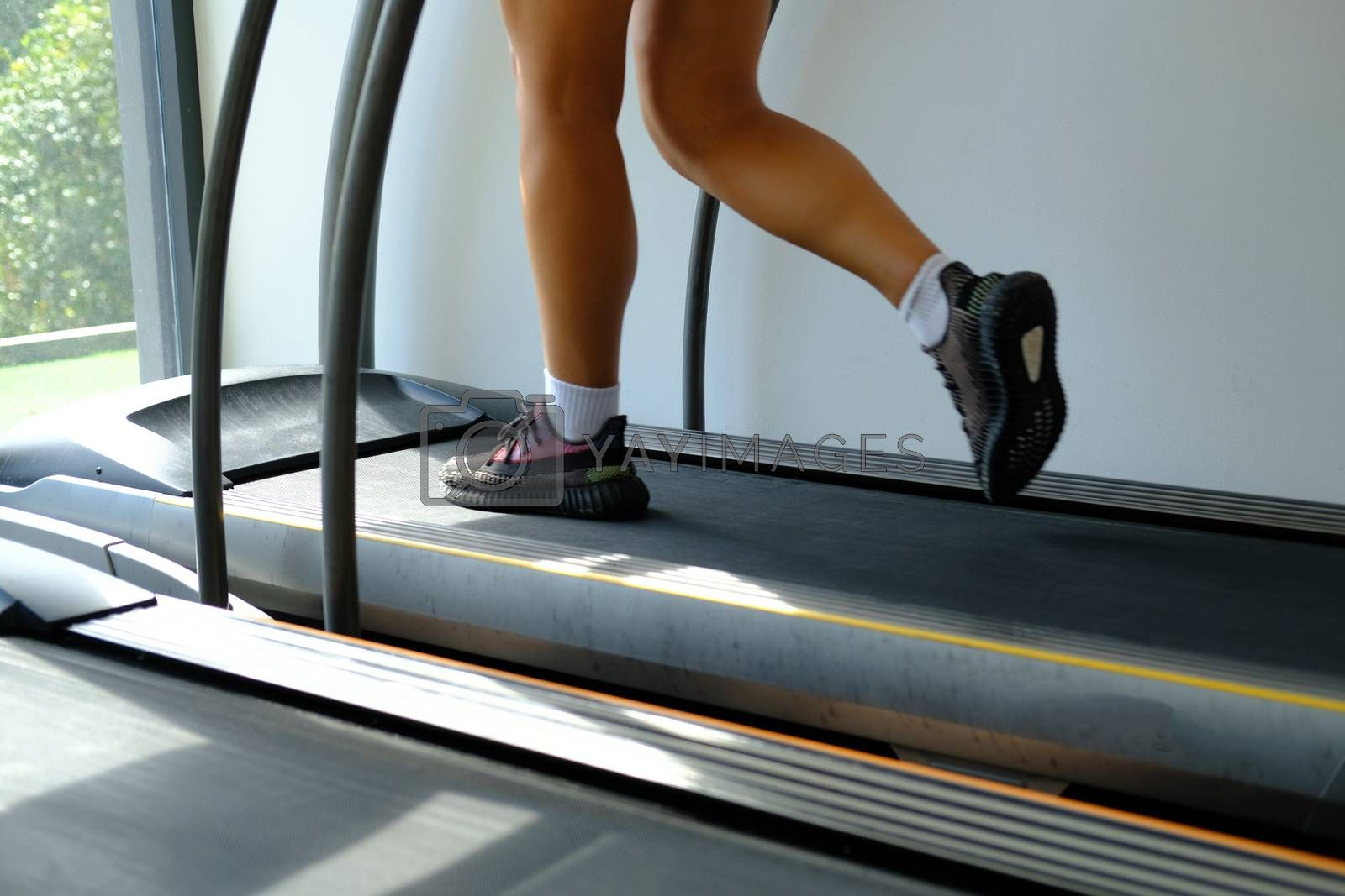 Fitness girl running on track treadmil. Health and sport concept background. Woman with muscular legs in gym workout at fitness gym.