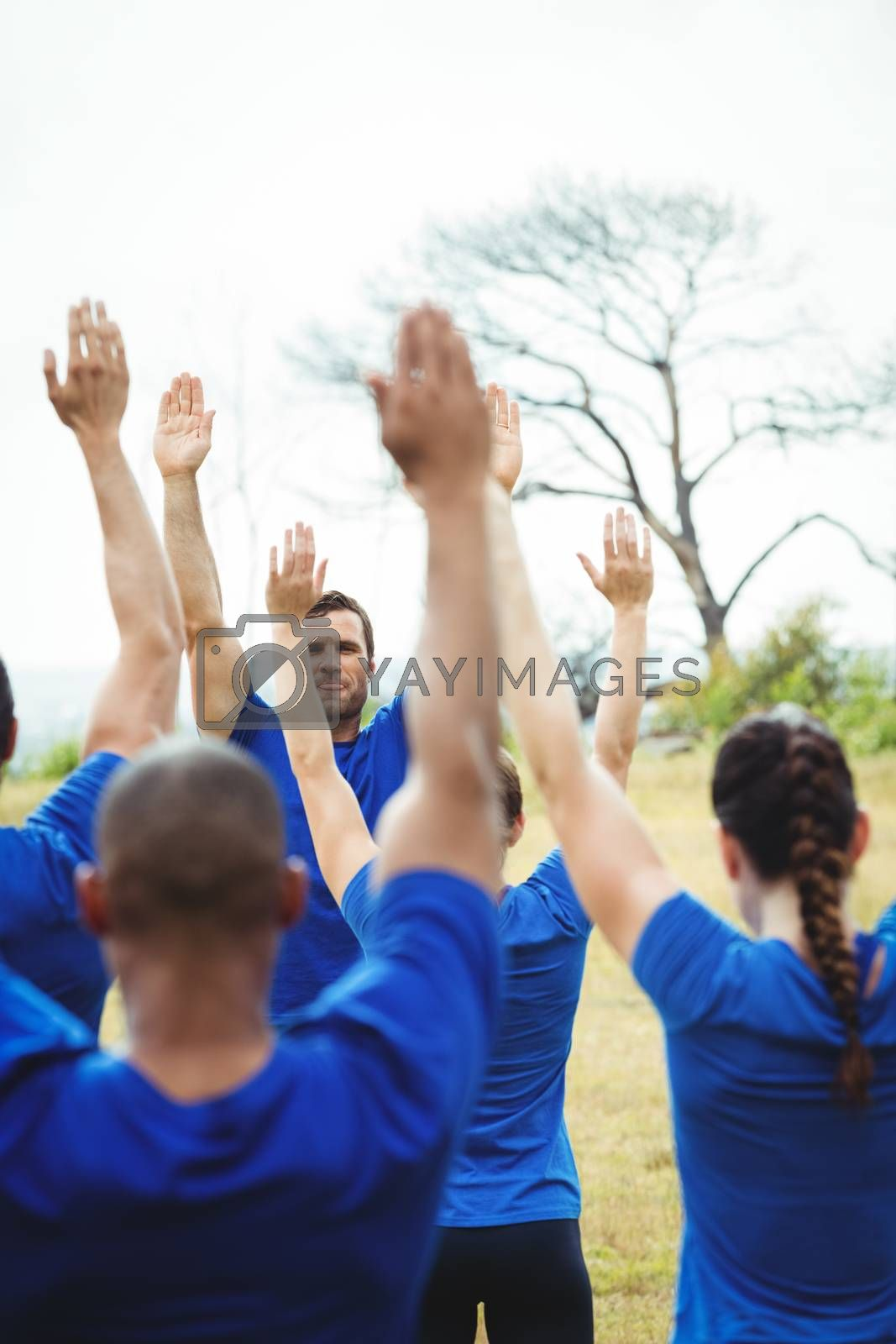 Fit people performing stretching exercise in bootcamp