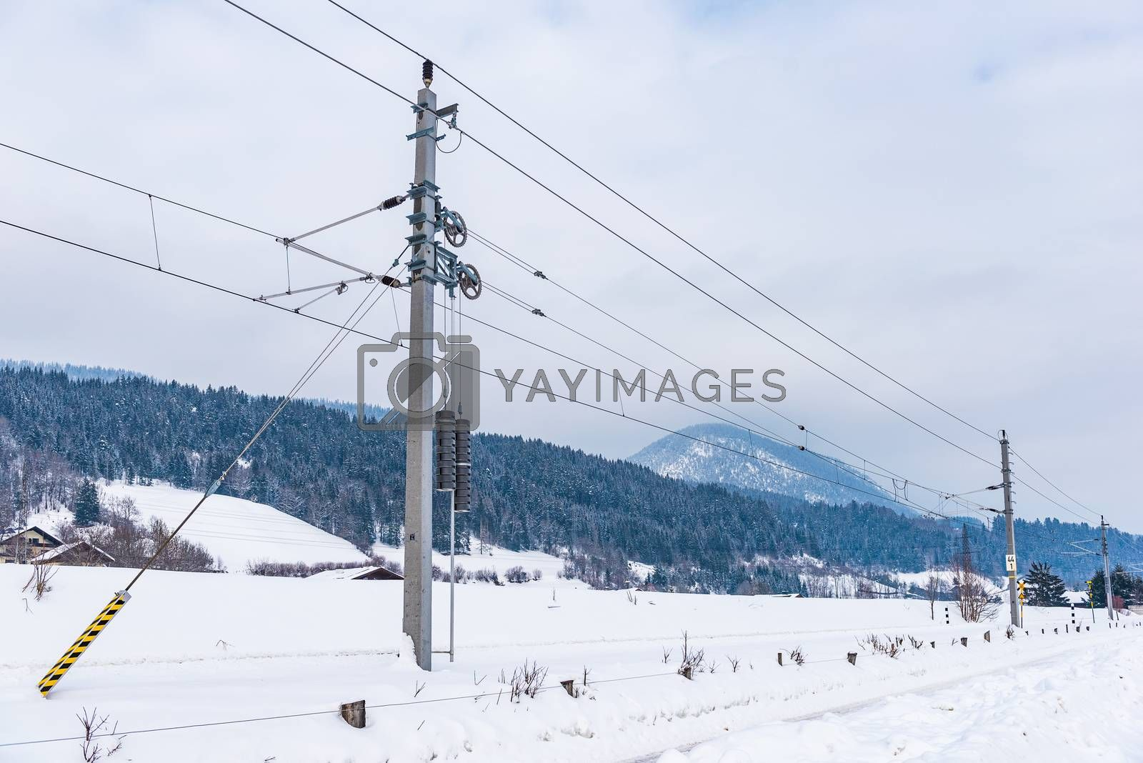 Railway electrification system - electric power overhead line network, pylon against cloudy, blue sky and mountains in winter.