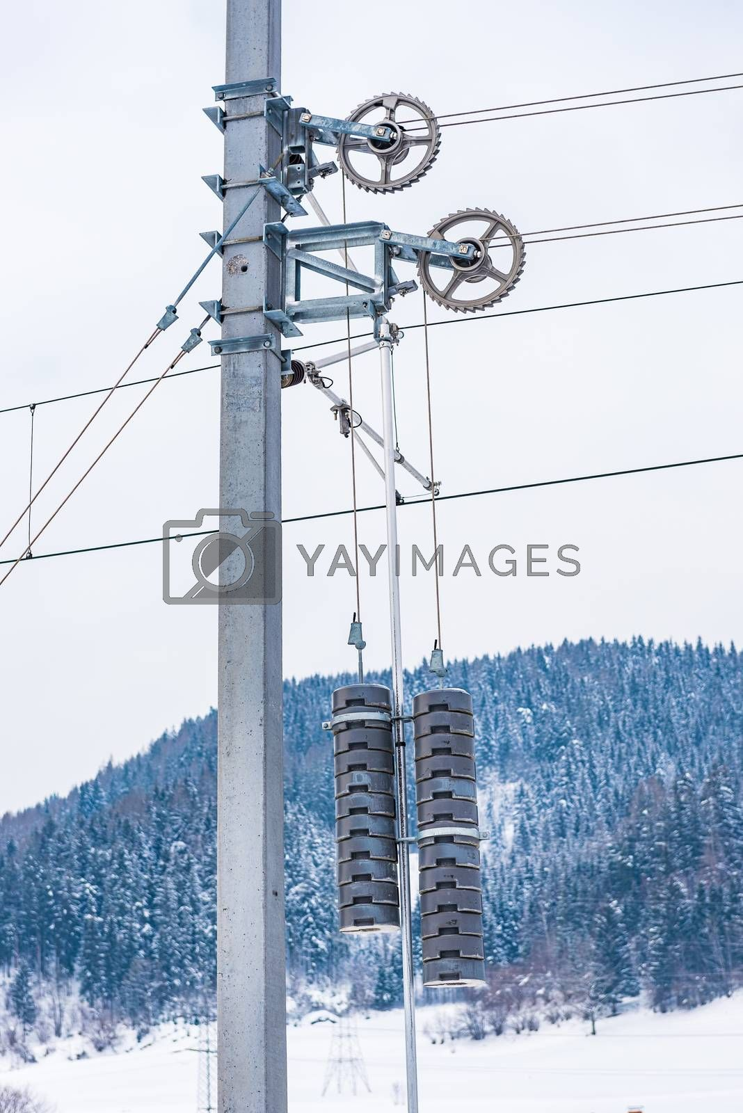 Railway electrification system details. Electric power overhead line, steel pylon with concrete counterweights hanging from a pulley system, keeps railroad overhead catenary wires in correct tension