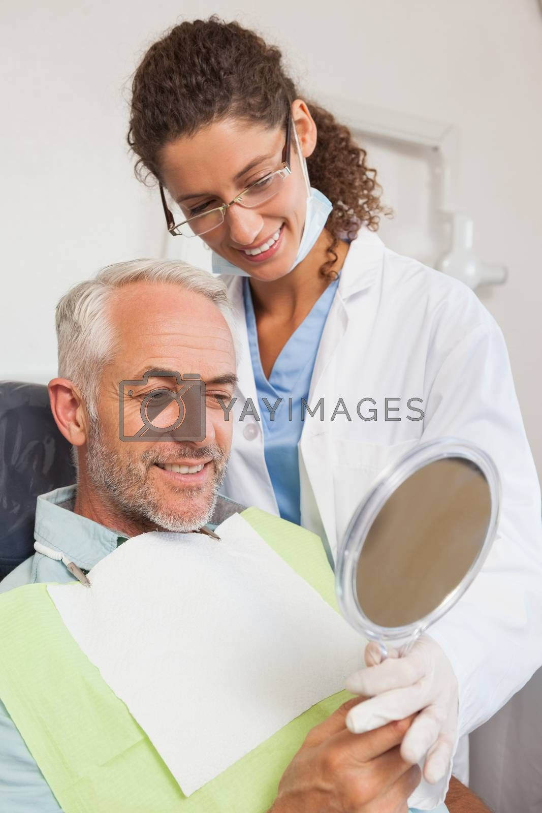 Patient admiring his new smile in the mirror at the dental clinic