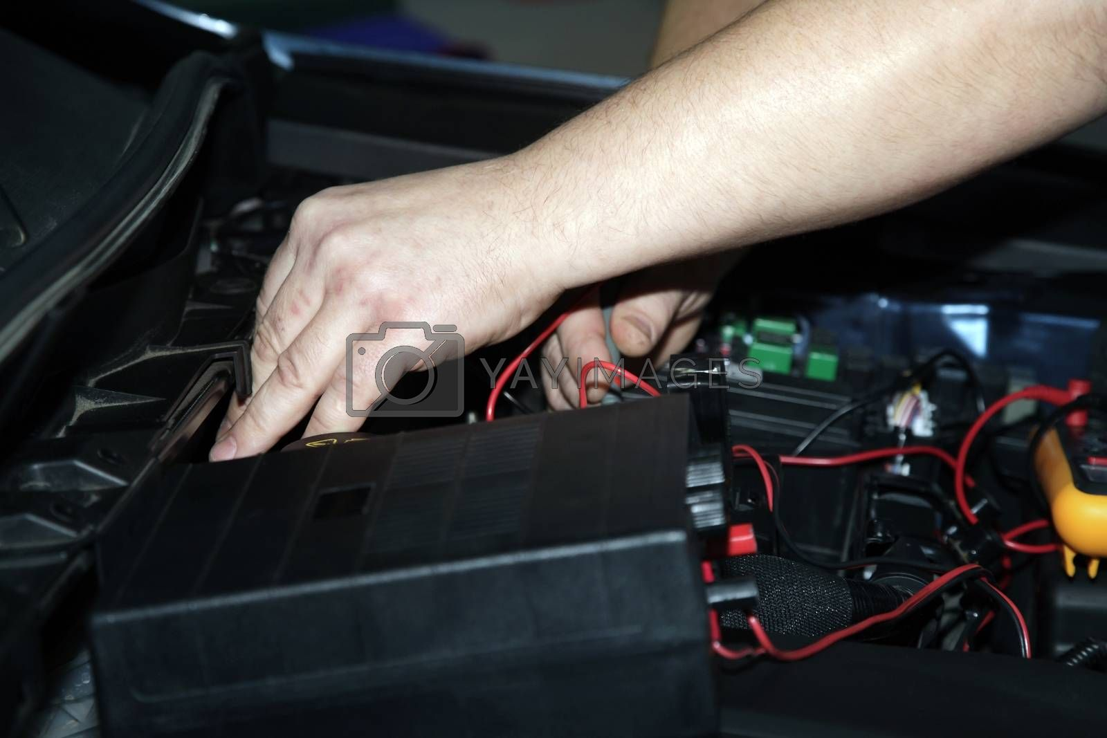 Male hands performing car repair with open hood