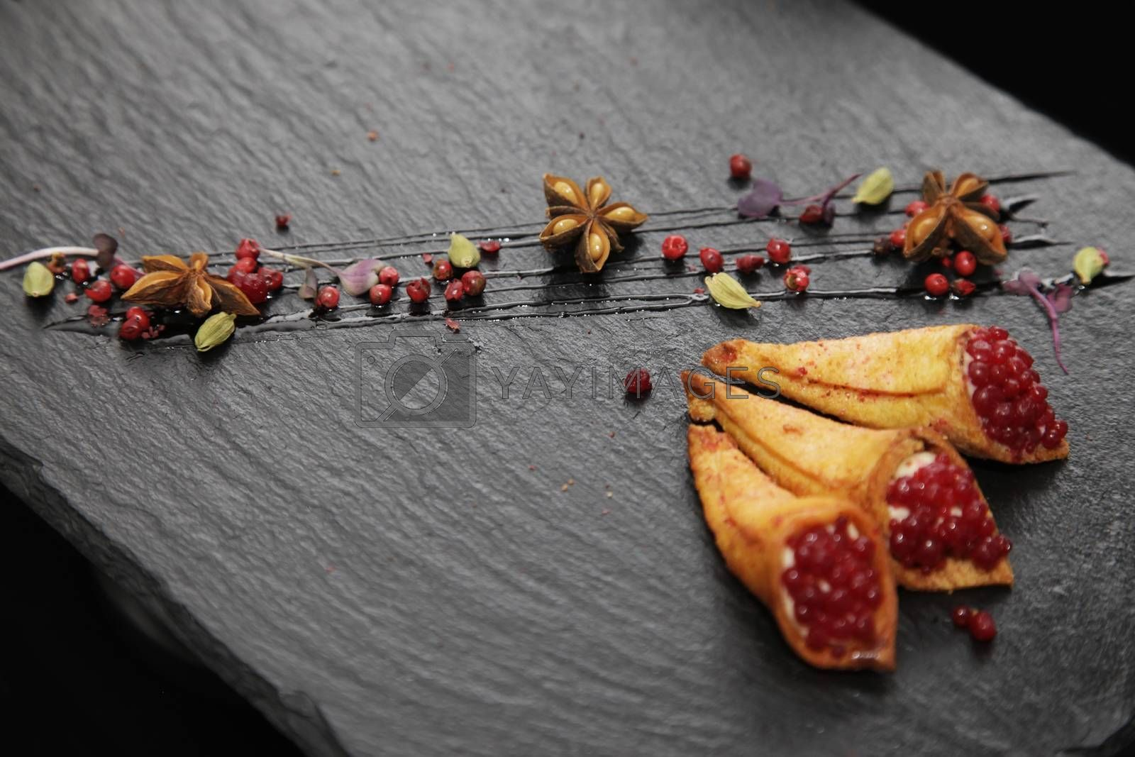 Rabbit pate in crispy horns decorated with spices on a black stone plate