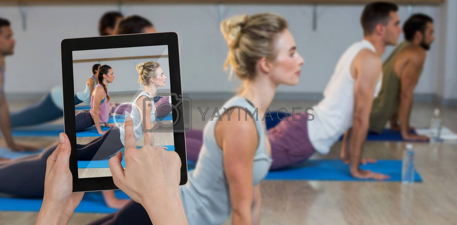 Hands touching digital tablet against white background against side view of people performing yoga