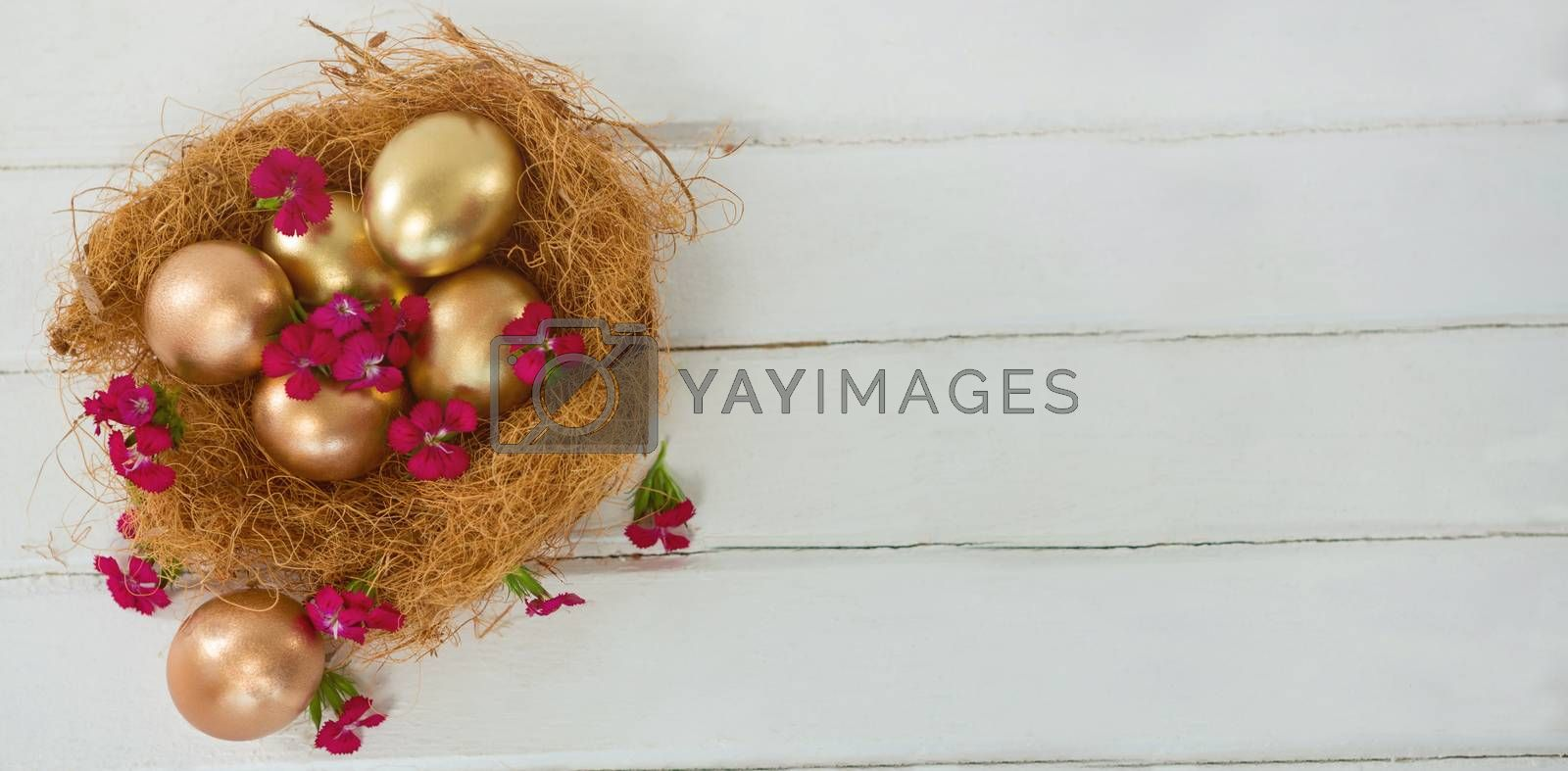 High angle view of golden Easter eggs in nest on wooden table