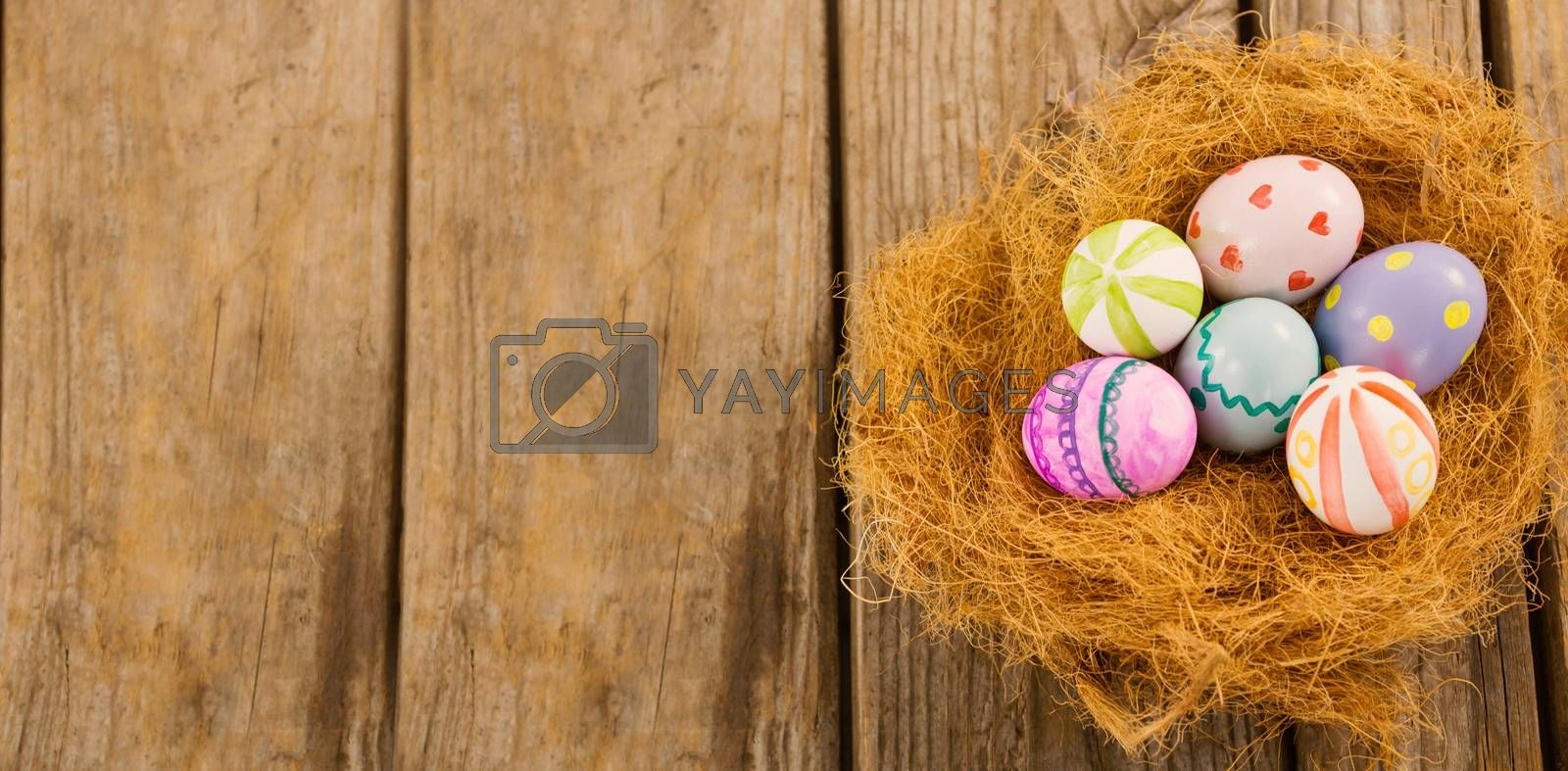 Painted Easter eggs in nest on wooden background
