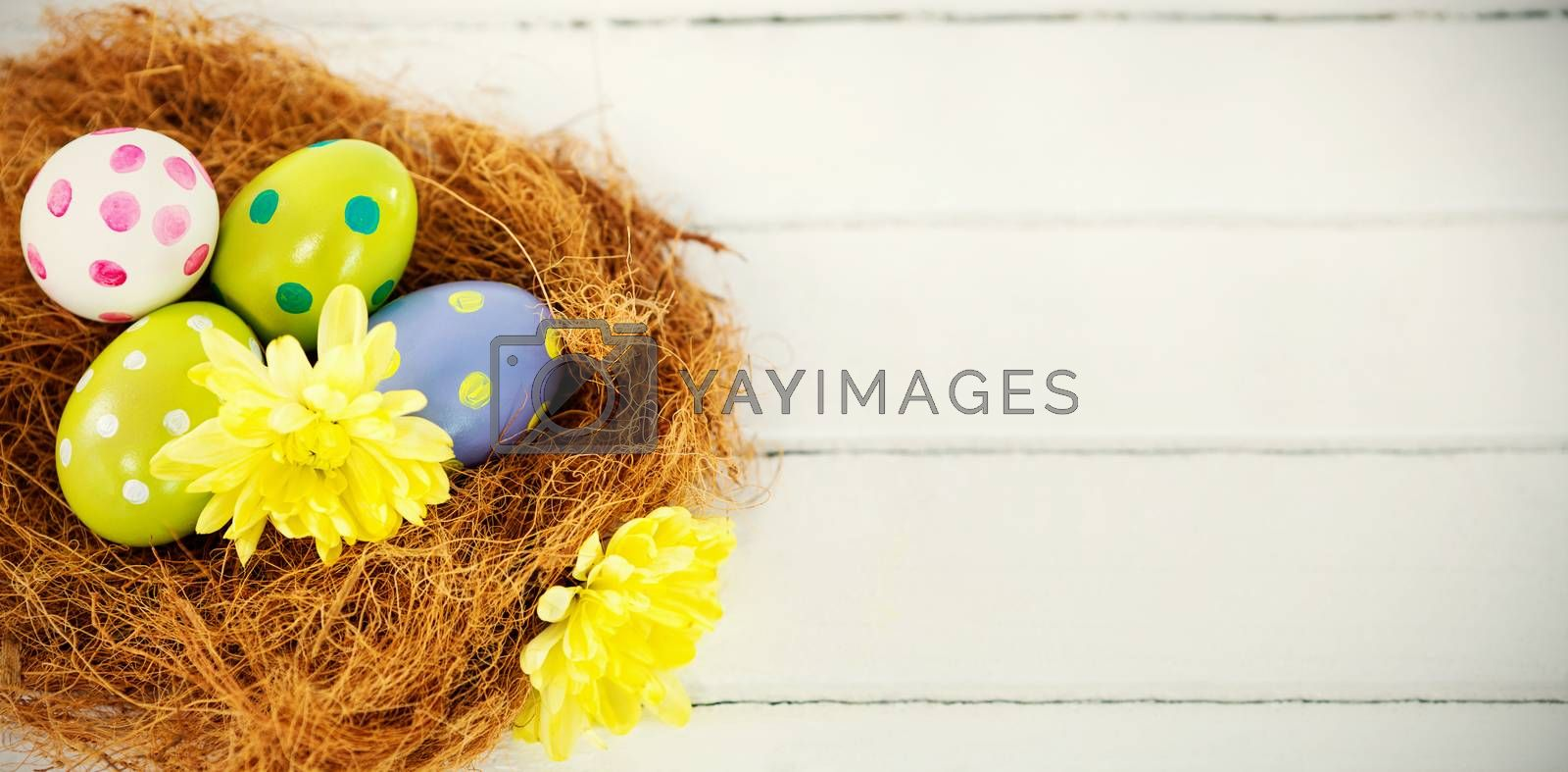 Close-up of painted Easter eggs in nest on wooden table