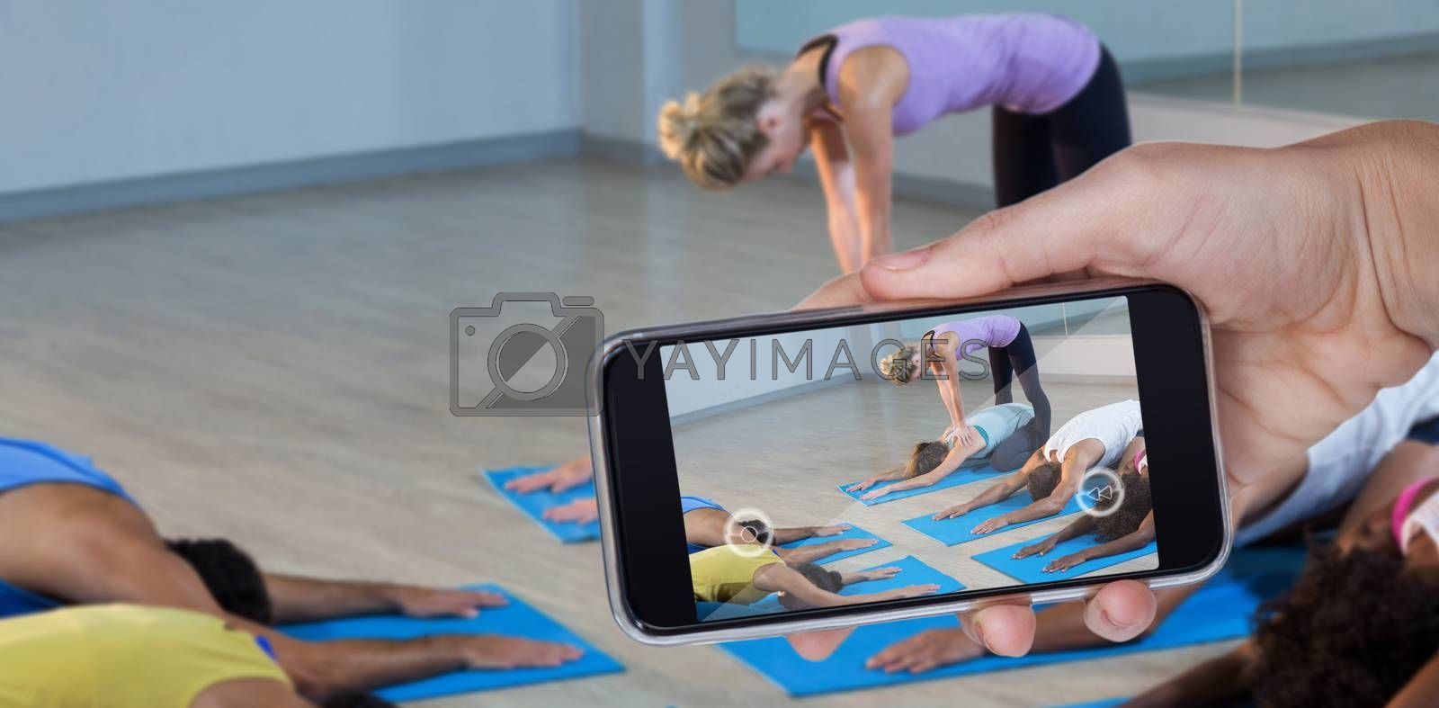 Hand holding mobile phone against white background against yoga instructor helping student with correct pose