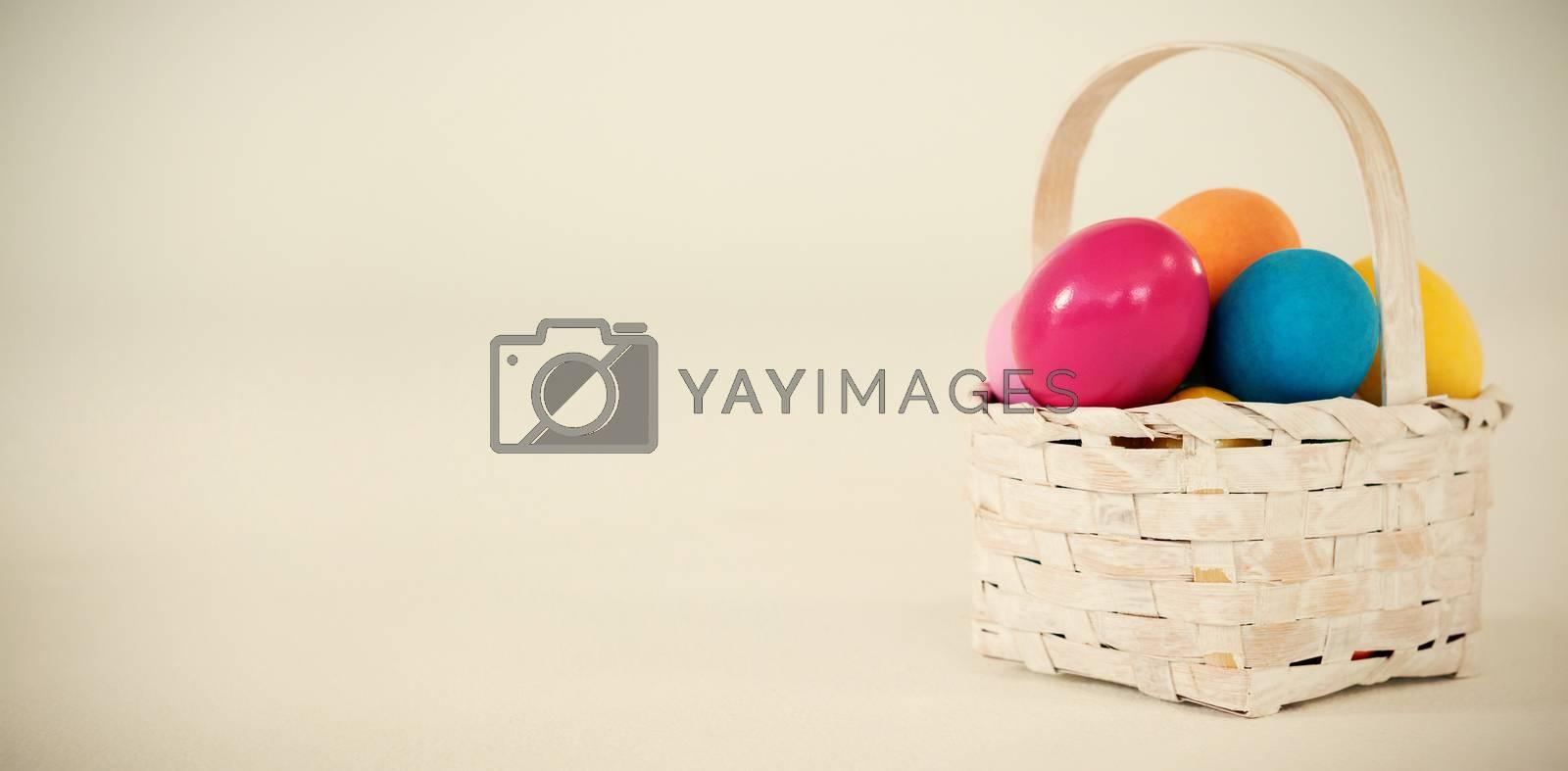 Various Easter eggs in wicker basket on white background
