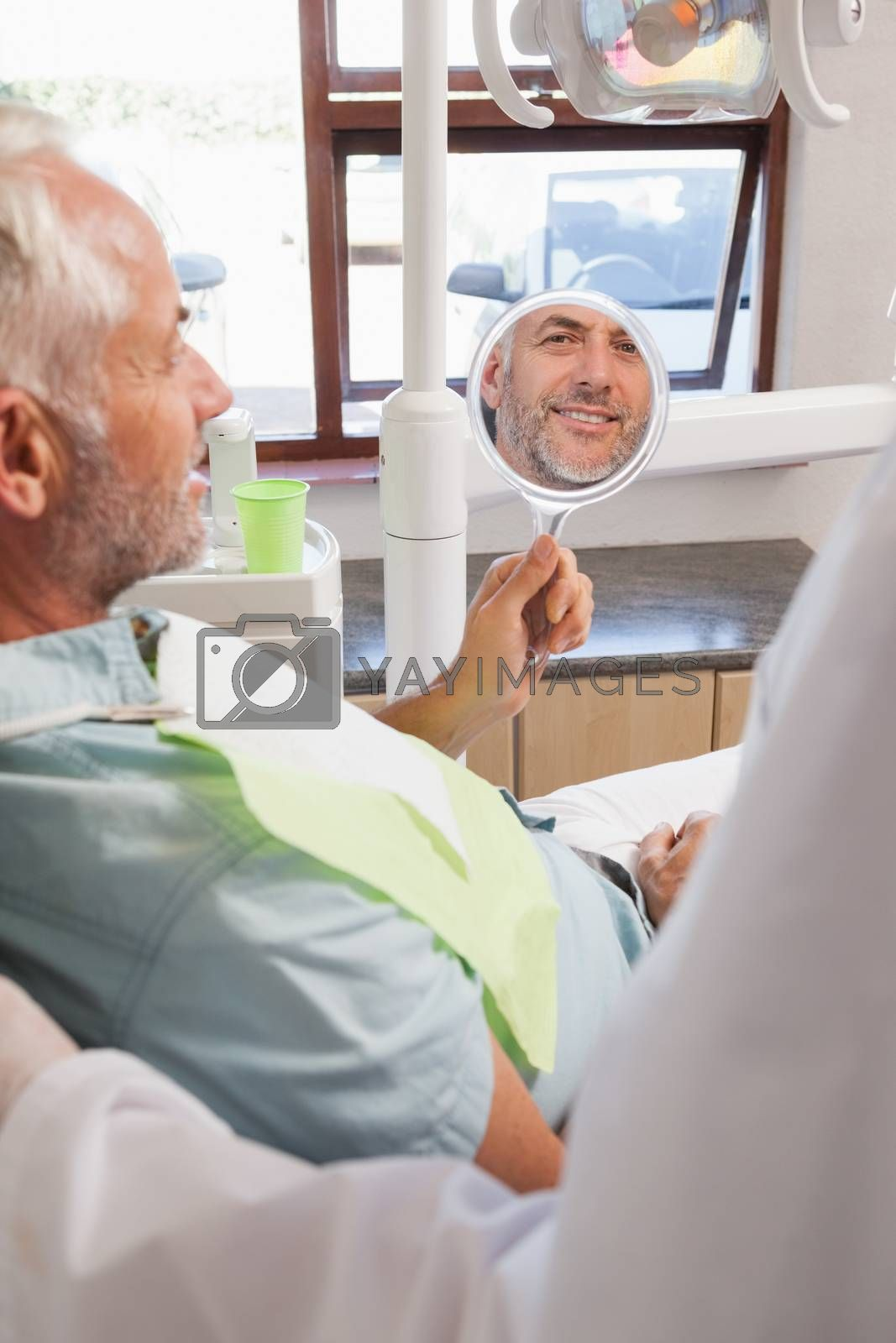 Patient admiring new smile in the mirror at the dental clinic