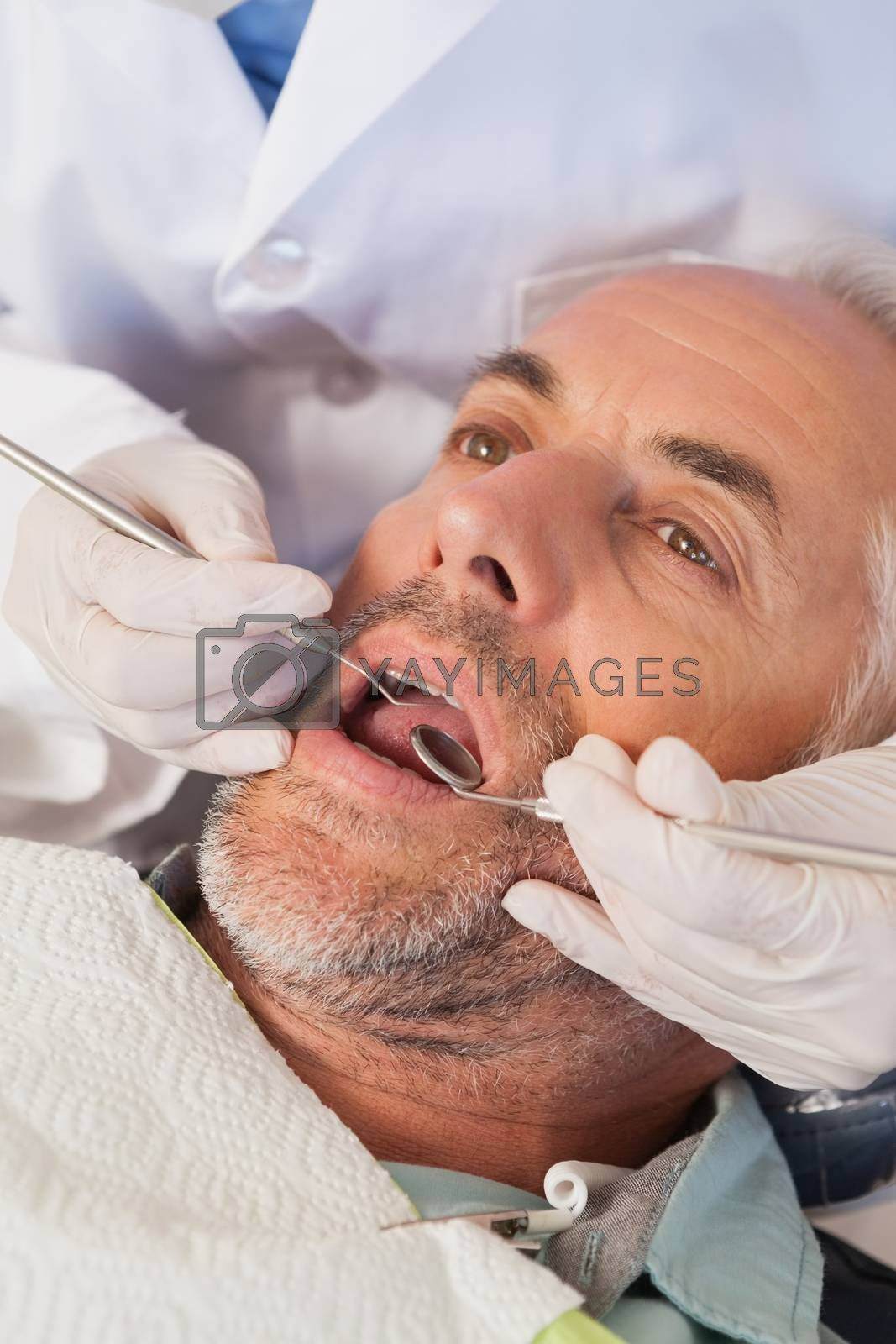 Dentist examining a patients teeth in the dentists chair at the dental clinic