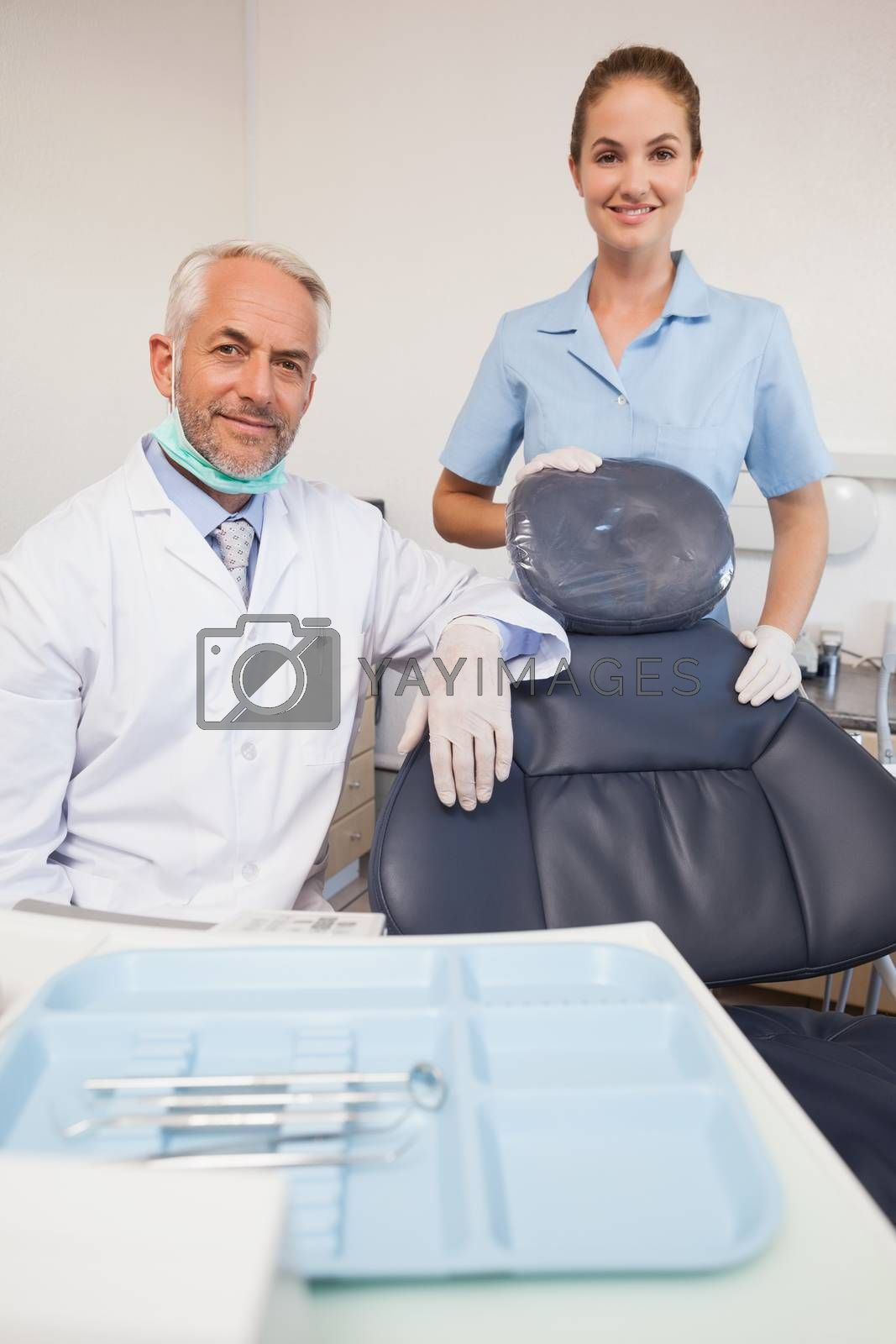 Dentist and assistant smiling at camera by Wavebreakmedia