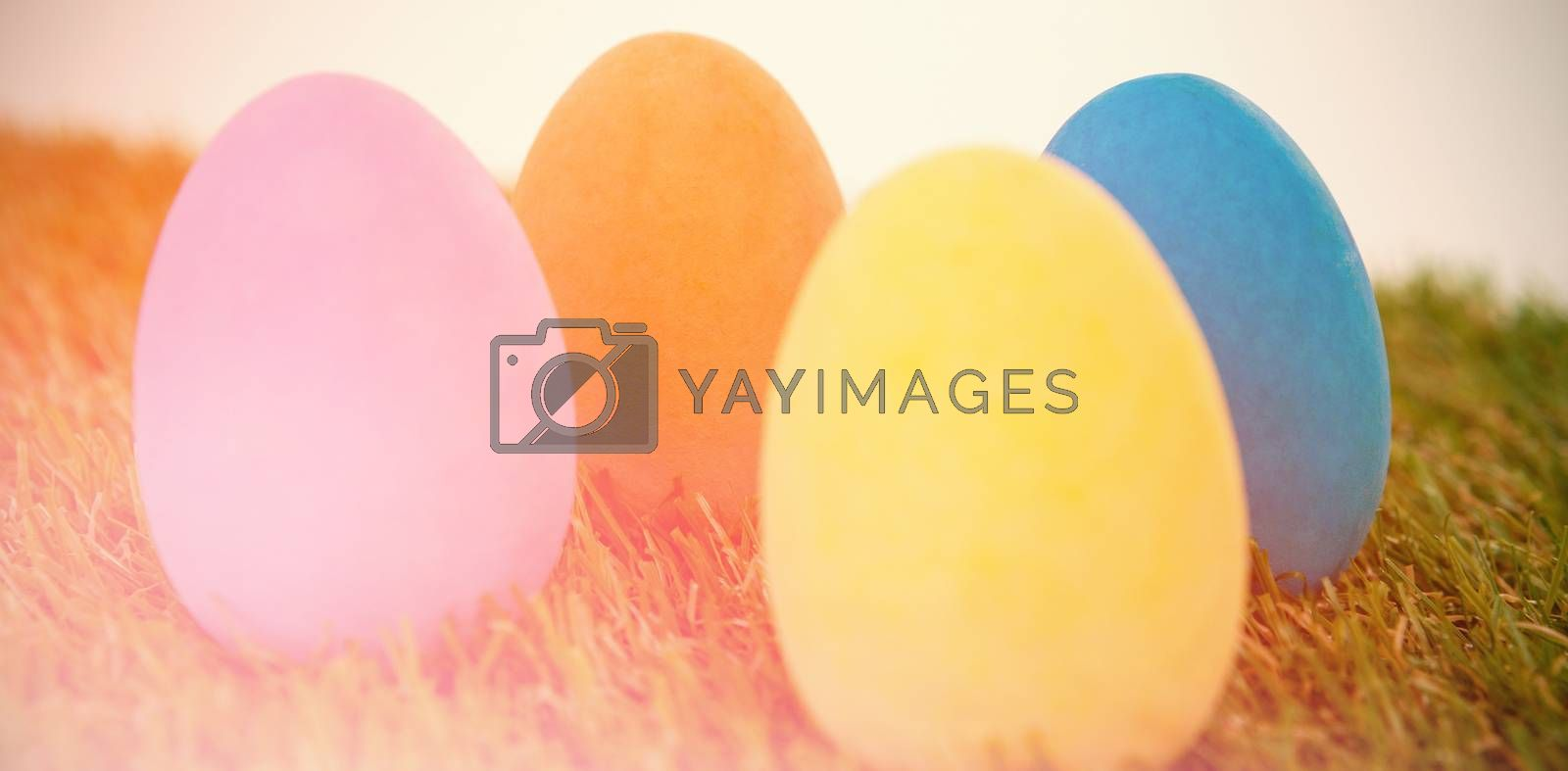 Painted Easter eggs arranged on grass against white background