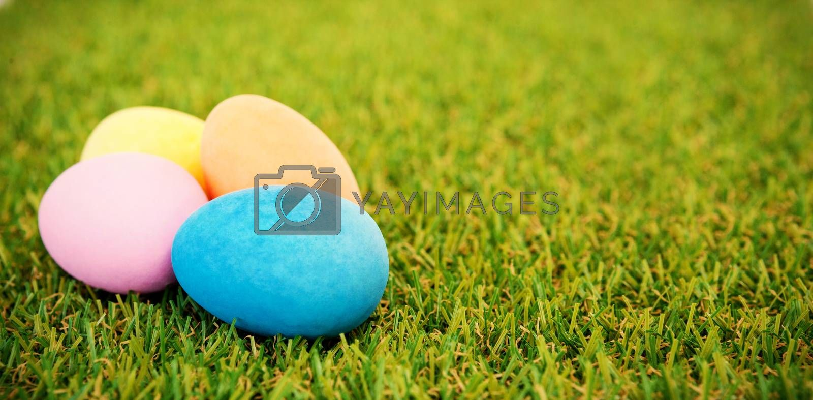 Various painted Easter eggs arranged on grass