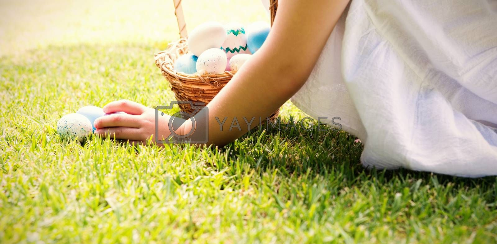 Little girl collecting easter eggs outside in the garden