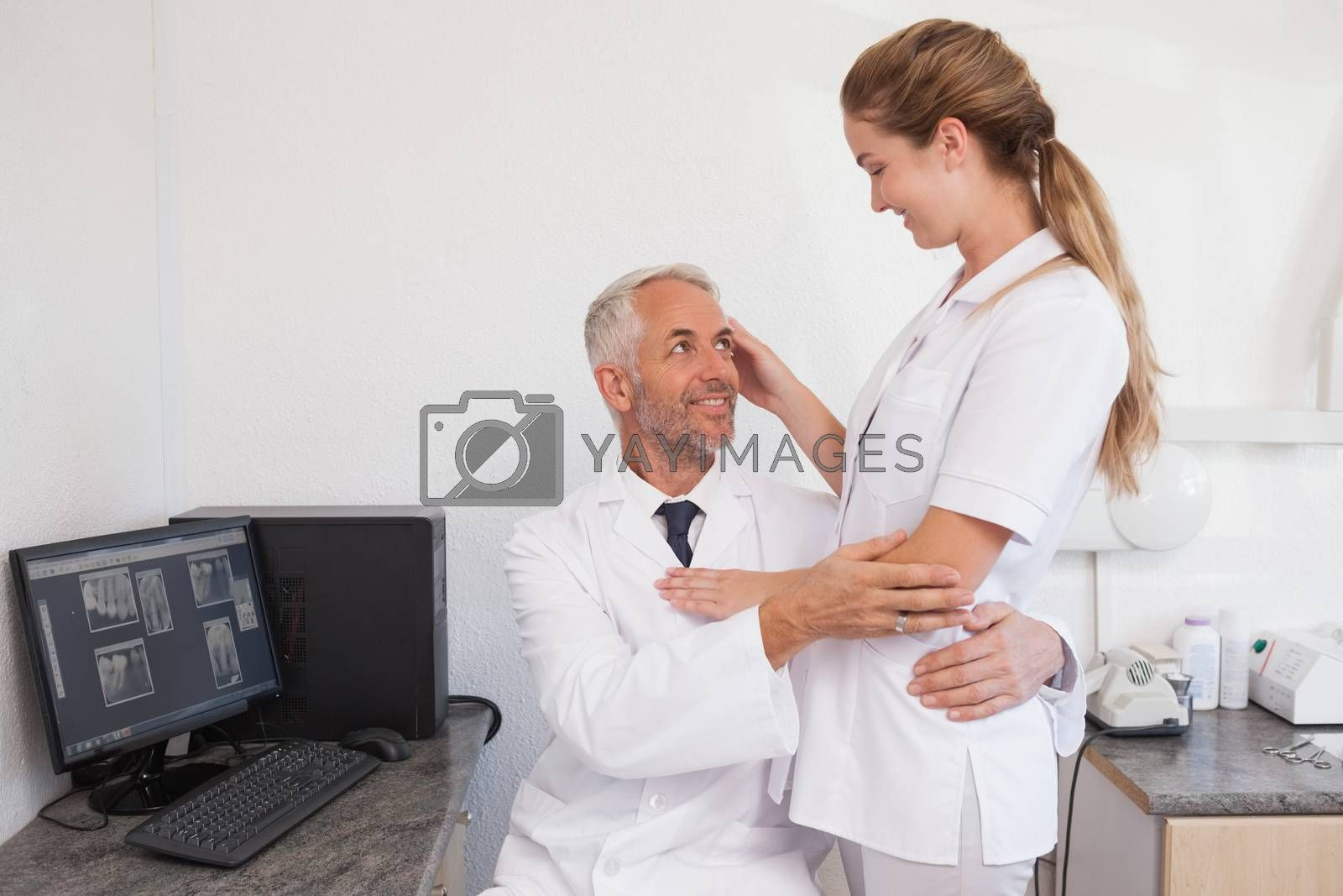Dentist and dental assistant embracing inappropriately at the dental clinic