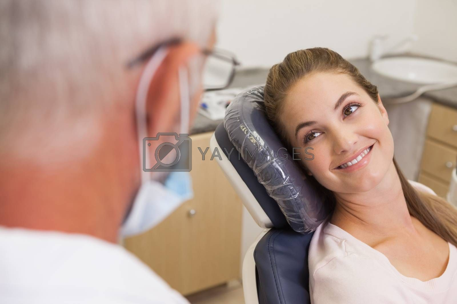 Dentist and patient smiling at each other at the dental clinic