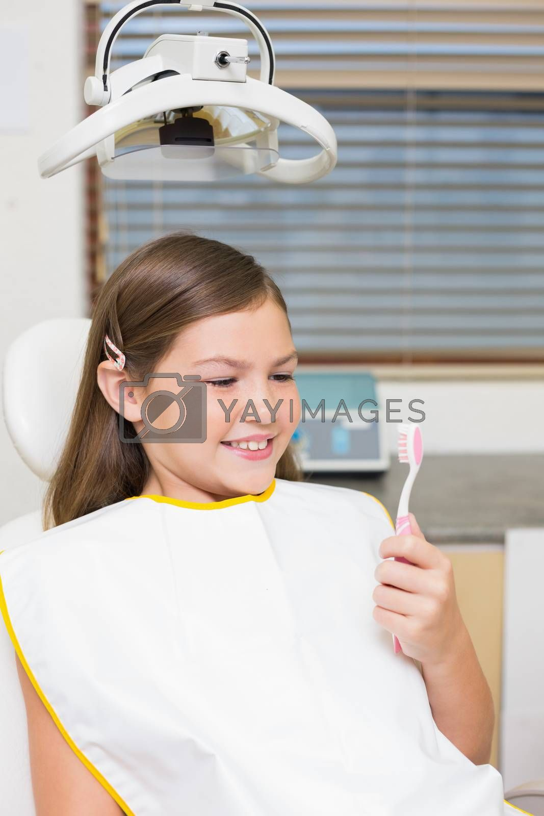 Little girl holding toothbrush in dentists chair at the dental clinic