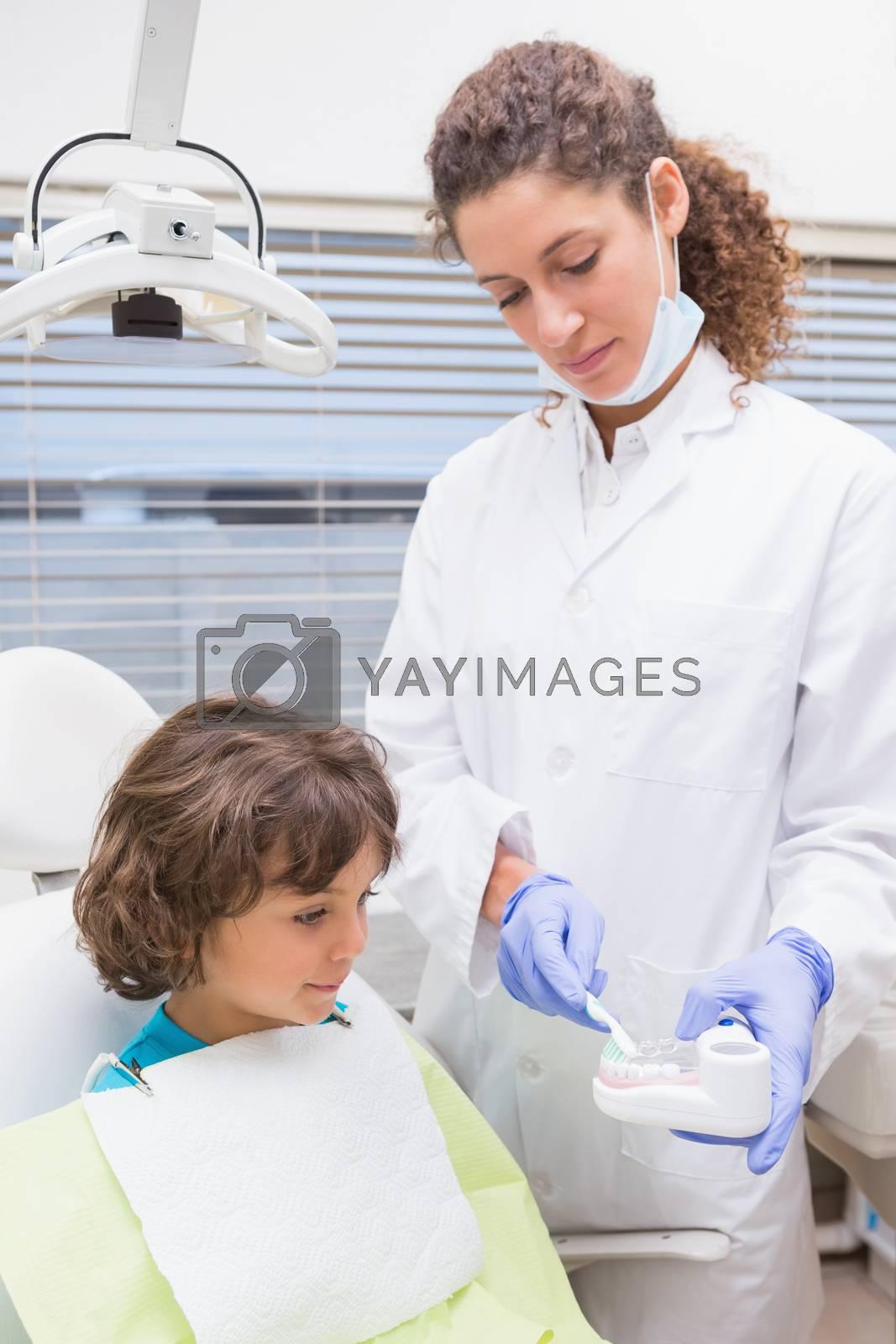 Pediatric dentist showing little boy teeth model at the dental clinic