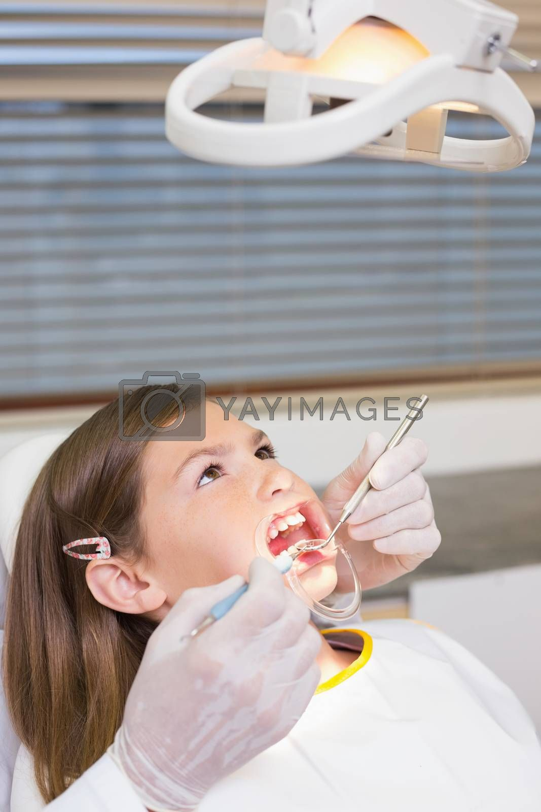 Dentist using mouth retractor on little girl at the dental clinic