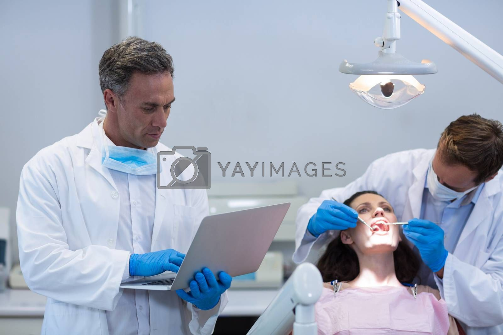 Dentist using laptop while colleague examining a female patient at dental clinic